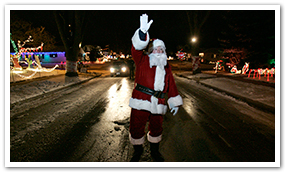 Santa Claus walking in a Candy Cane Lane street.